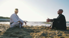 Two professional karate fighters meditating on the beach sea background Stock Footage