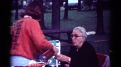 1964: a family seated outdoors in lawn chairs enjoying a picnic CALIFORNIA Stock Footage