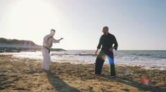 Two professional karate fighters on the beach sea background, slow motion Stock Footage