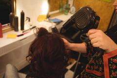 Hair stylist blow drying womans hair Stock Photos