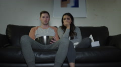 Medium shot of couple on sofa watching sad movie on television / Cedar Hills, Stock Footage