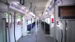 Walking between seats in almost empty Kuala Lumpur train driving to Batu Caves Stock Footage
