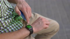 Man hand using his gadgets smart watch, smartphone sitting on bench green screen Stock Footage