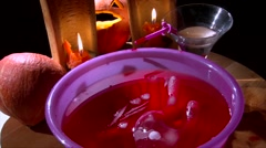 Scooping red drink with hand, Halloween decorated dinner table Stock Footage