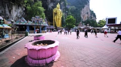 Walking towards entrance to Batu Caves with the amazing gold Murugan statue, KL Stock Footage