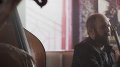 Medium panning shot of strings duo playing in bar / Salt Lake City, Utah, United Stock Footage