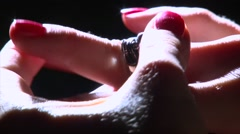 Take off rough ring with silver skull on girl hand, black smoke Stock Footage