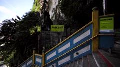 Tourists go towards the Dark Cave in Batu Caves, Kuala Lumpur, Malaysia Stock Footage