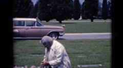 1968: a woman kneeling alone at a grave site with a car in the background Stock Footage