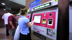 Caucasian girl buys train ticket using ticket machine in the KL Sentral Station Stock Footage