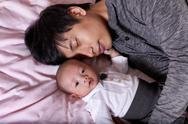 Restless infant baby boy with his sleeping father Stock Photos
