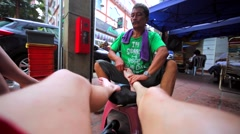 Street masseuse does massage of male legs and feet in Kuala Lumpur market. Stock Footage