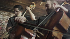 Medium panning low angle view of men playing bass and cello in bar / Salt Lake Stock Footage