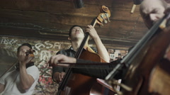 Slow motion medium low angle view of strings trio playing in bar / Salt Lake Stock Footage