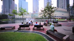 Promenade area in front of the Petronas Towers. People enjoy beautiful fountain Stock Footage