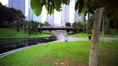 Panoramic view of park near Petronas Towers. Pond, statue of whale, skyscrapers Stock Footage