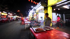 Malaysian man fries bacon, cooks grilled food at Jalan Alor street in KL Stock Footage
