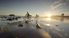 Young couple mountain biking on Pacific ocean beach, Oregon Stock Footage