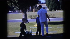 1968: father speaking to two sons in graveyard by gravesite CLARKSDALE, ARIZONA Stock Footage