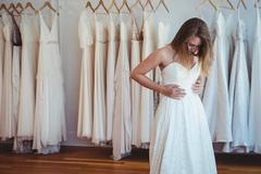Beautiful woman trying on wedding dress in a shop Stock Photos