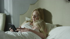 Medium panning shot of mother reading e-book to daughter in bed / Cedar Hills, Stock Footage