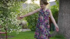 Medium panning shot of girl dancing in yard / Springville, Utah, United States Stock Footage
