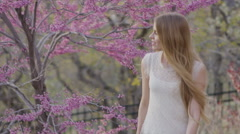 Medium slow motion panning shot of woman smelling flowers in park / Cedar Hills, Stock Footage