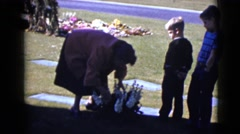 1968: two boys quietly watch as a woman straightens up a bouquet of flowers  Stock Footage