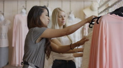 Medium panning shot of women examining skirt in clothing store / American Fork, Stock Footage