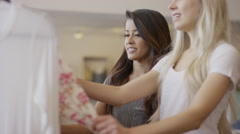Medium low angle panning shot of women examining dress in clothing store / Stock Footage