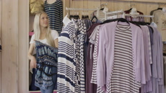 Medium panning shot of woman gathering dresses in clothing store / American Stock Footage