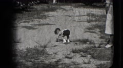 1942: child trying to walk on the sand watched by a woman and a little girl  Stock Footage