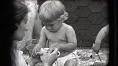 1942: mothers feeding their toddlers sitting on a mat NEW YORK Stock Footage