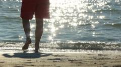 Man walking on sandy sea shore Stock Footage