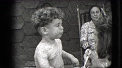 1942: shirtless little toddler is being spoon fed by his mother  Stock Footage