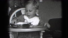 1942: small kid is trying to eat his food NEW YORK Stock Footage