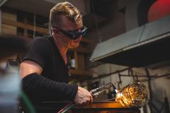 Glassblower giving final touch to a piece of glass with glassblowing torch Stock Photos