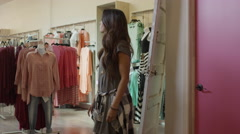 Medium panning shot of friend approving dress of friend in clothing store / Stock Footage