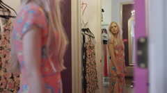 Medium panning shot of woman examining dress in clothing store mirror / American Stock Footage