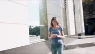 Young woman in jeans with smartphone walking in the city, steadicam shot Stock Footage