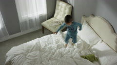 Medium high angle shot of mother catching son jumping on bed / Cedar Hills, Stock Footage