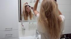 Medium Shot Woman brushing hair in bathroom Stock Footage