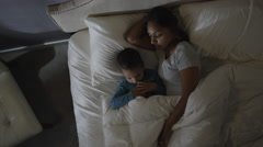Medium high angle shot of mother and son sleeping in bed / Cedar Hills, Utah, Stock Footage