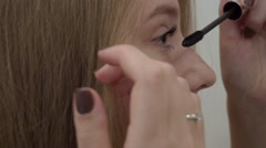 Portrait of woman apply mascara on eyelashes in bathroom mirror at home Stock Footage