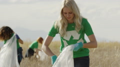 Medium panning shot of volunteers collecting garbage in field / Vineyard, Utah, Stock Footage