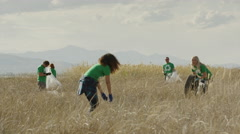 Wide panning shot of volunteers throwing tire in field / Vineyard, Utah, United Stock Footage