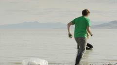 Wide panning shot of volunteers collecting tire in lake / Vineyard, Utah, United Stock Footage