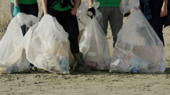 Wide tilt up shot of proud volunteers posing with garbage at beach / Vineyard, Stock Footage