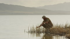 Wide shot of park ranger collecting water sample from lake / Vineyard, Utah, Stock Footage