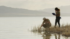 Wide shot of park rangers collecting water sample from lake / Vineyard, Utah, Stock Footage